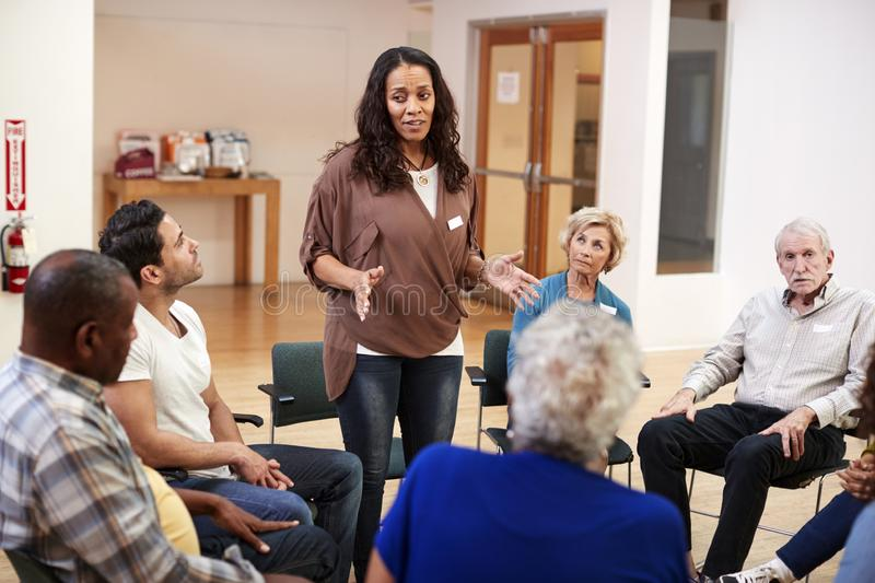 Woman Standing To Address Self Help Therapy Group Meeting In Community Center stock photo