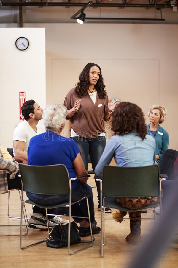 Woman Standing To Address Self Help Therapy Group Meeting In Community Center stock photography