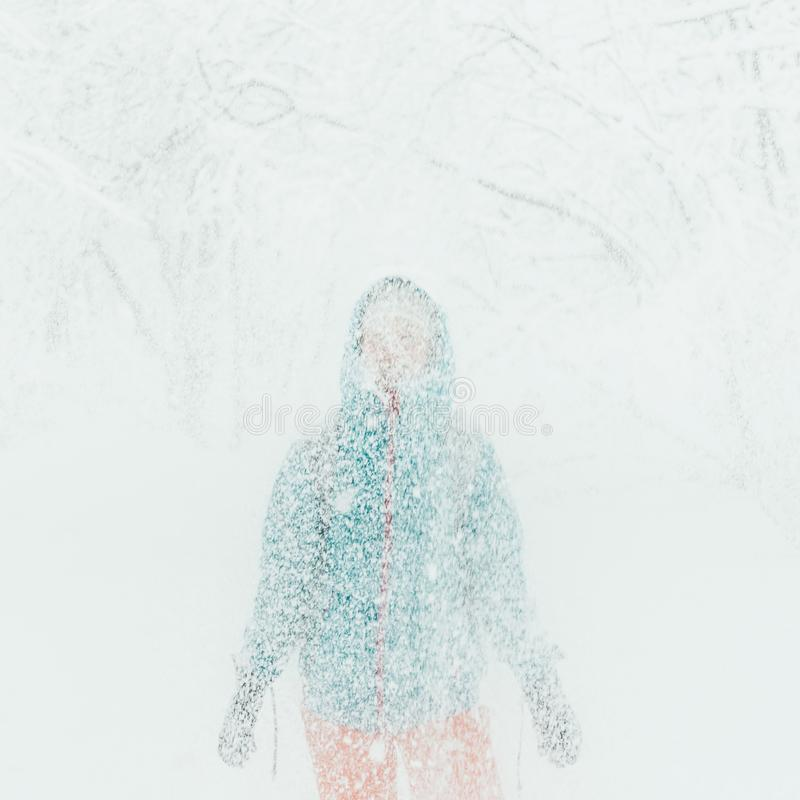 Woman standing under falling snow. royalty free stock photos