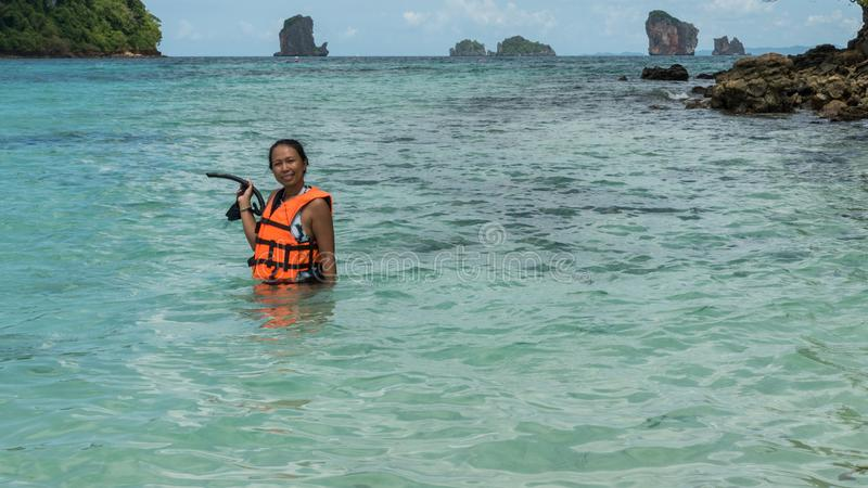 Woman standing in water in orange life jacket. Holding mask and snorkle stock image