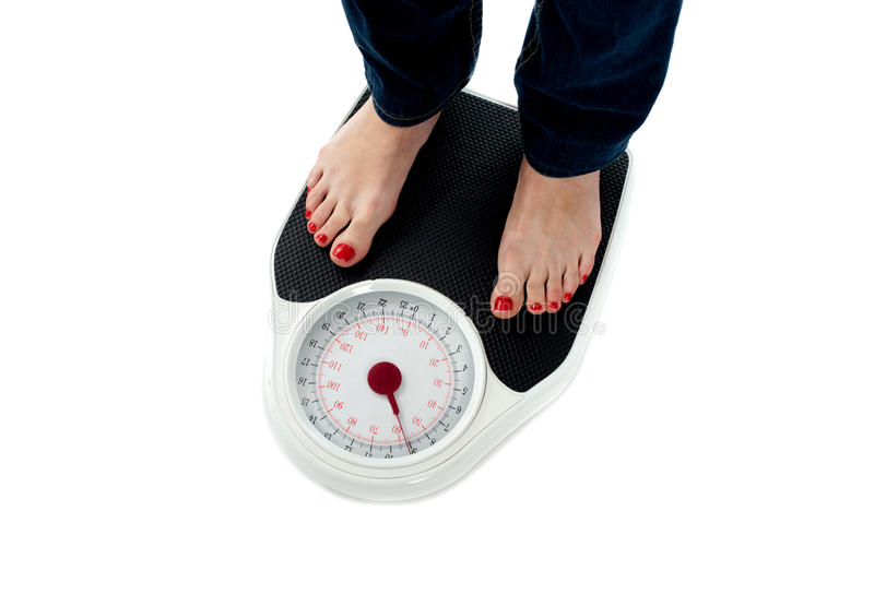 Woman standing on weighing scale, closeup of legs