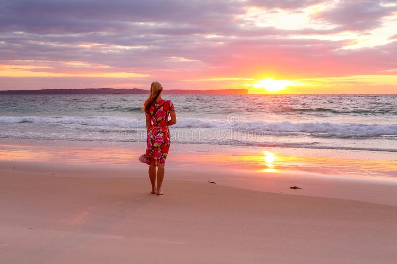 Woman standing on the wet sand of the beach watching sunrise stock photos