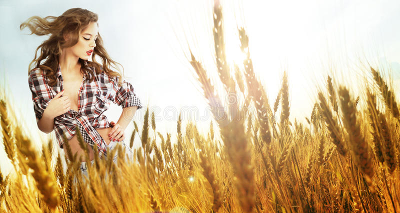 Woman standing in a wheat field royalty free stock photo