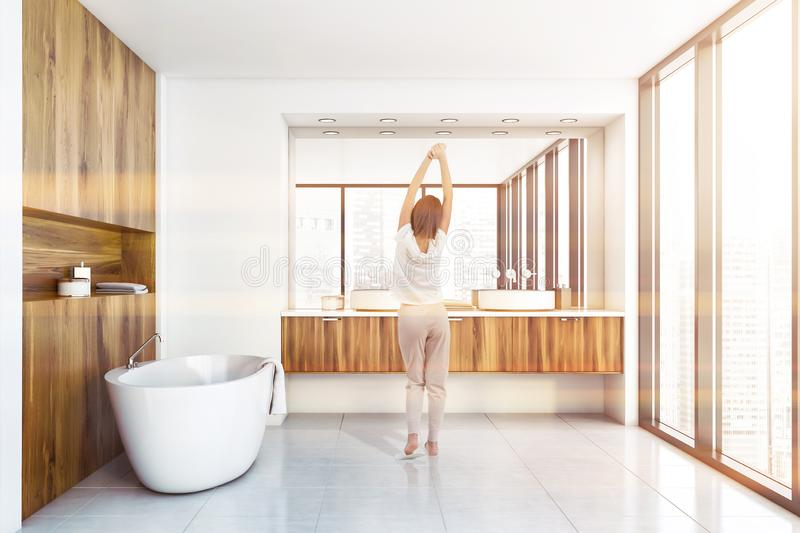 Woman standing in white sunlit bathroom. Young woman standing in luxury sunlit bathroom with wooden and white walls, panoramic window, tiled floor, comfortable royalty free stock image