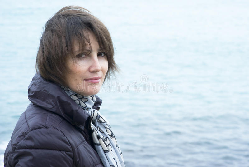 Woman standing in windy conditions in front of the sea. Woman standing front the sea stock photos
