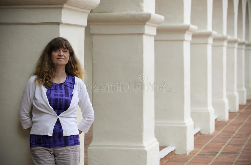 A Woman Stands Amid Spanish Revival Style Architecture stock images