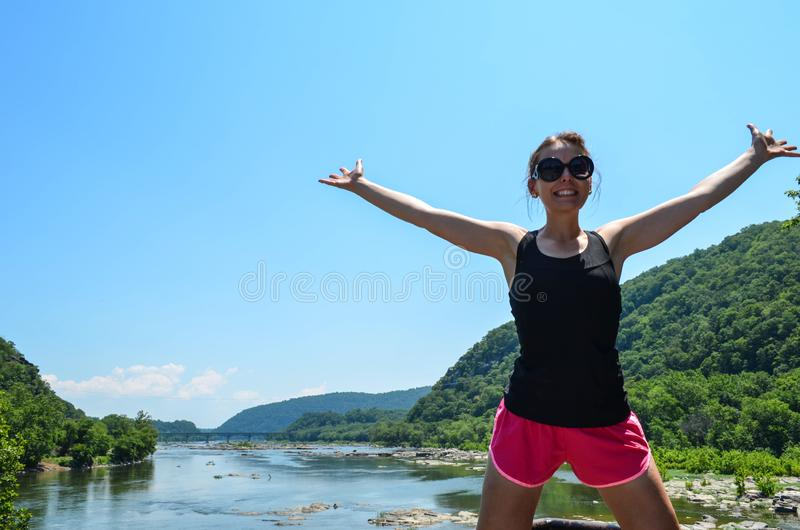 Woman stands with arms raised, from Maryland Heights of the Potomac River from Harpers Ferry West Virginia, concept for freedom. And happiness, wearing running royalty free stock image