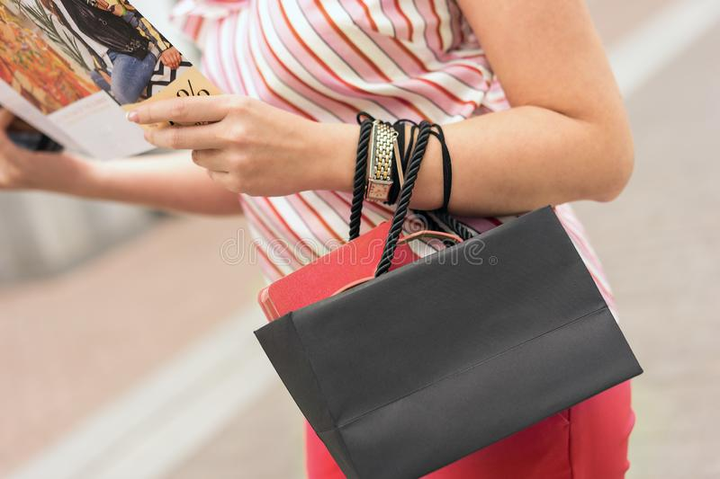 A woman stands with a black paper bag in her hands and an advertising booklet. Shopping concept. Living coral. Space for text on t stock image