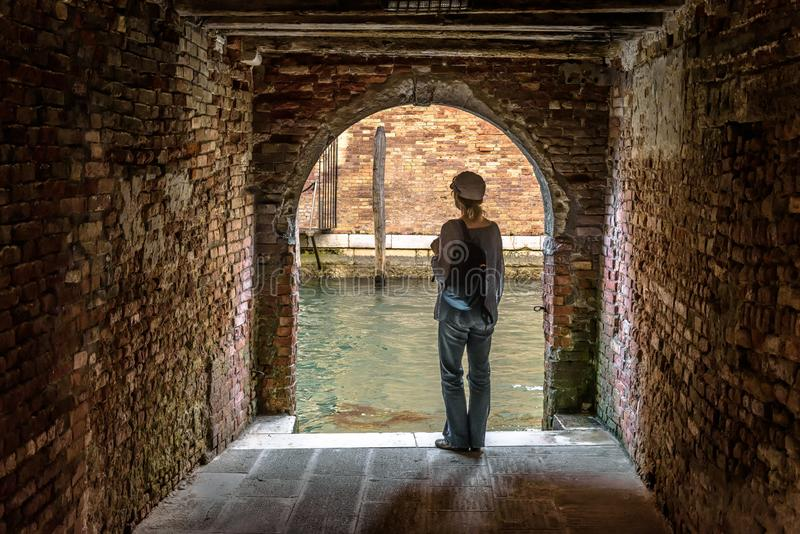 Woman stands at exit to canal from courtyard, Venice, Italy stock images