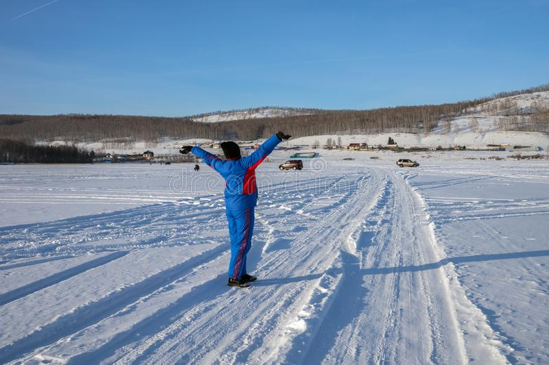A woman stands, holding up her hands, in a winter lake against the backdrop of the shore and fishermen. Winter landscape. A woman stands, holding up her hands stock image