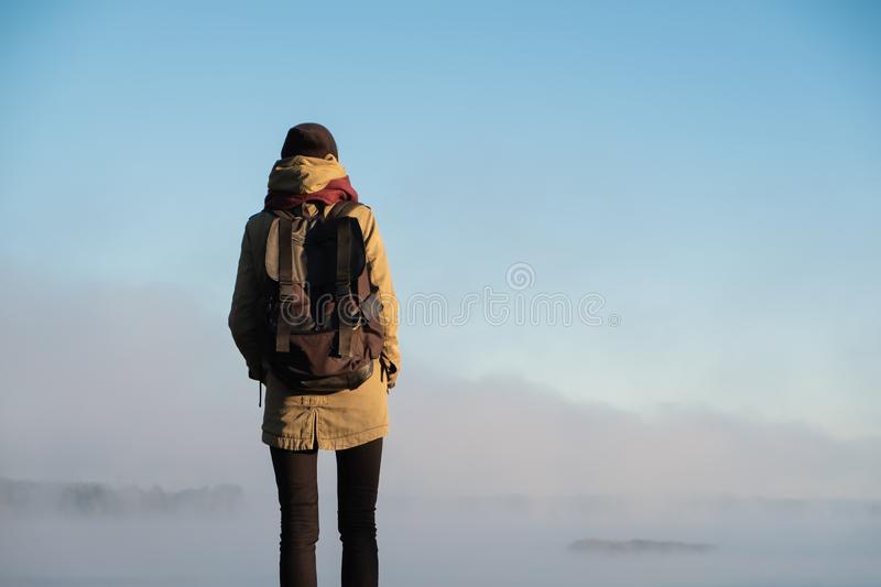 Woman stands in morning sunlight in front of beautiful nature sc. Enery covered in fog. Female hiker enjoying rising sun in misty natural background royalty free stock photography