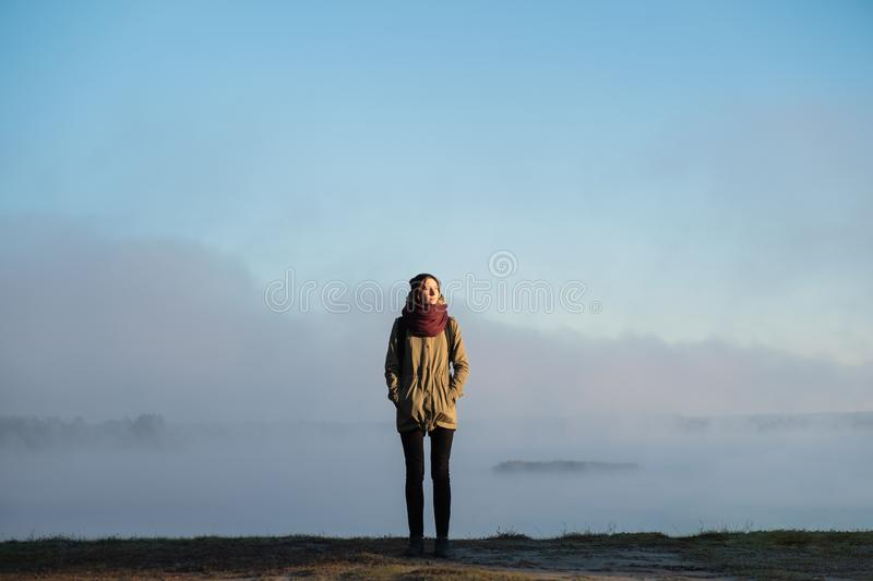 Woman stands in morning sunlight in front of beautiful nature sc. Enery covered in fog. Female hiker enjoying rising sun in misty natural background royalty free stock photos