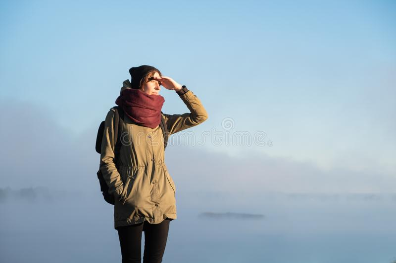 Woman stands in morning sunlight in front of beautiful nature sc. Enery covered in fog. Female hiker enjoying rising sun in misty natural background stock image