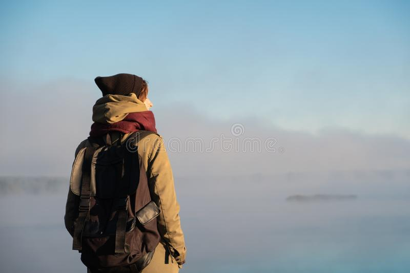 Woman stands in morning sunlight in front of beautiful nature sc. Enery covered in fog. Female hiker enjoying rising sun in misty natural background royalty free stock images