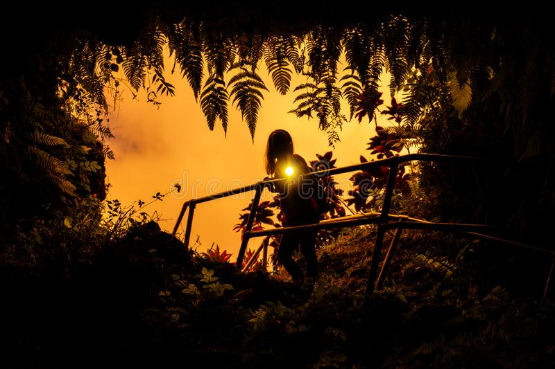 Woman stands near the entrance to the Lava Tube. Surrounded by lush tropical vegetation and flashes with the light of torch right into the camera. Maui, Hawaii stock image
