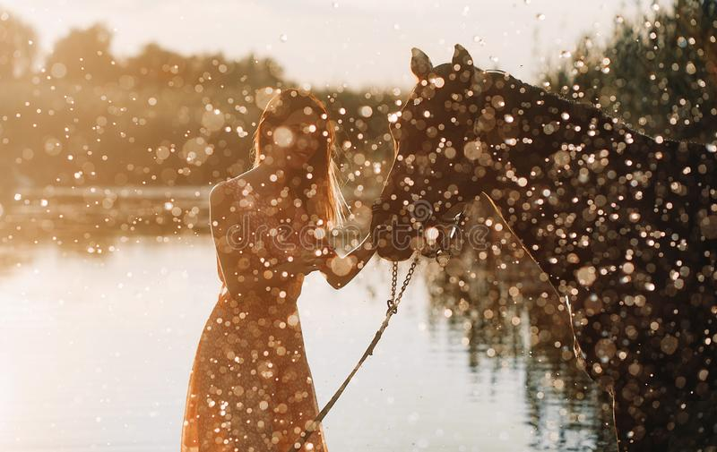 Woman stands next to the horse against background of the river and water splashes. A young woman stands next to the horse against background of the river and stock photo