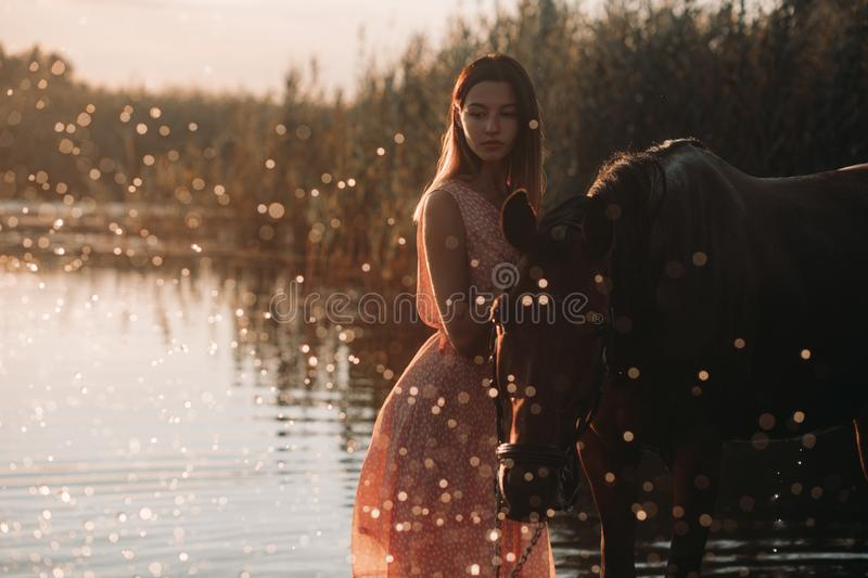 Woman stands next to the horse against background of the river and water splashes. A young woman stands next to the horse against background of the river and royalty free stock photos