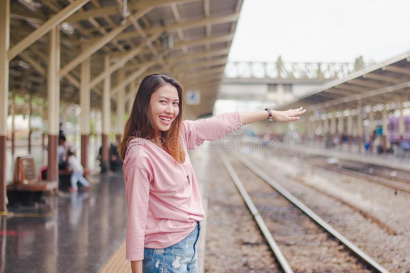 The woman extends her arms to the railroad tracks. stock image