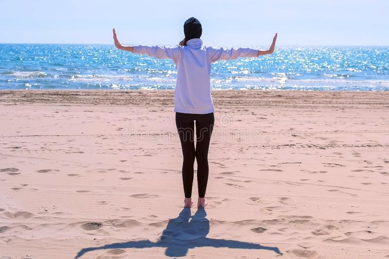 Woman stands on sand sea beach arms out to sides makes yoga exercise back view. Woman in hoodie, leggings and hat is standing on sand sea beach with arms out to royalty free stock photography