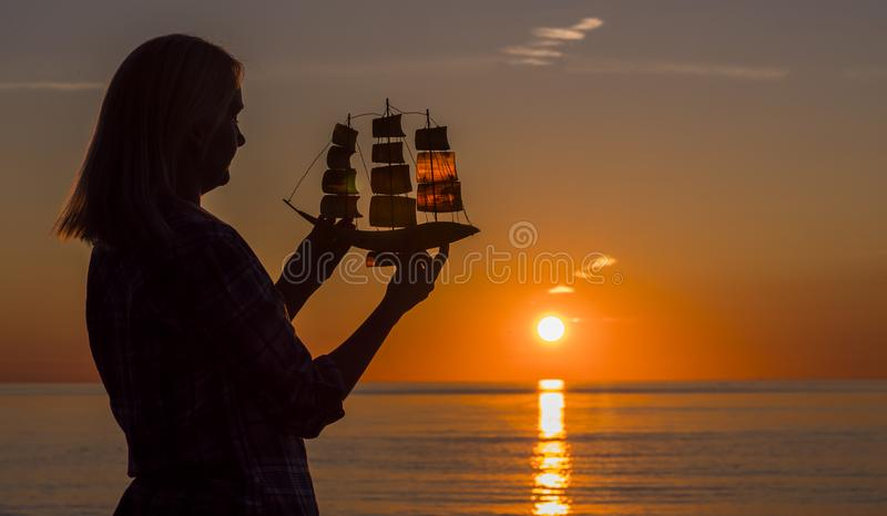 A woman stands by the sea at sunset, holds in her hands a model of a sailing ship. Hope and travel concept stock photo