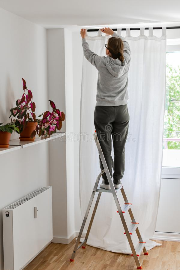 Woman hangs white curtains on the curtain rod royalty free stock photo