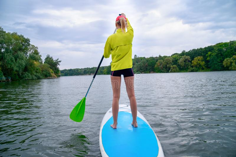 A woman stands on a SUP board on a large river on a cloudy day. Stand on the oars - great outdoor recreation stock images