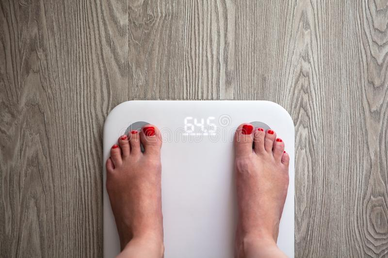 Woman stands on white modern electronic scales, which show 64.5 kg. Only feet are visible. Scales stand on gray wooden floor. royalty free stock images