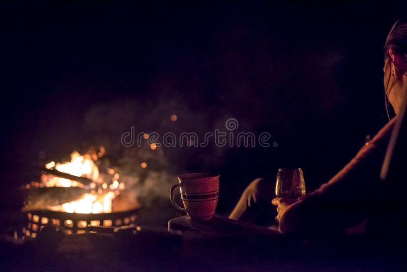 A woman stares at an outside roaring fire stock images