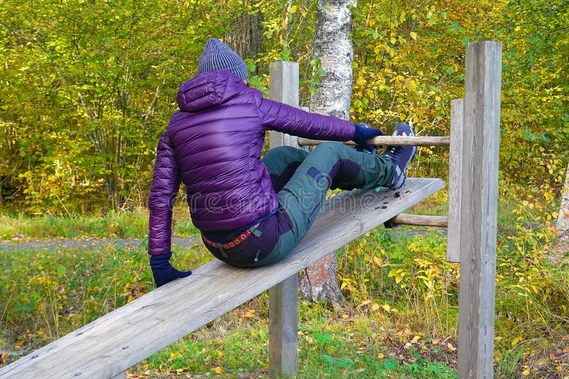 Woman start doing sit ups outdoor in park. Middle aged female enjoying beautiful autumn day, and increase her welfare by outdoor activities royalty free stock images
