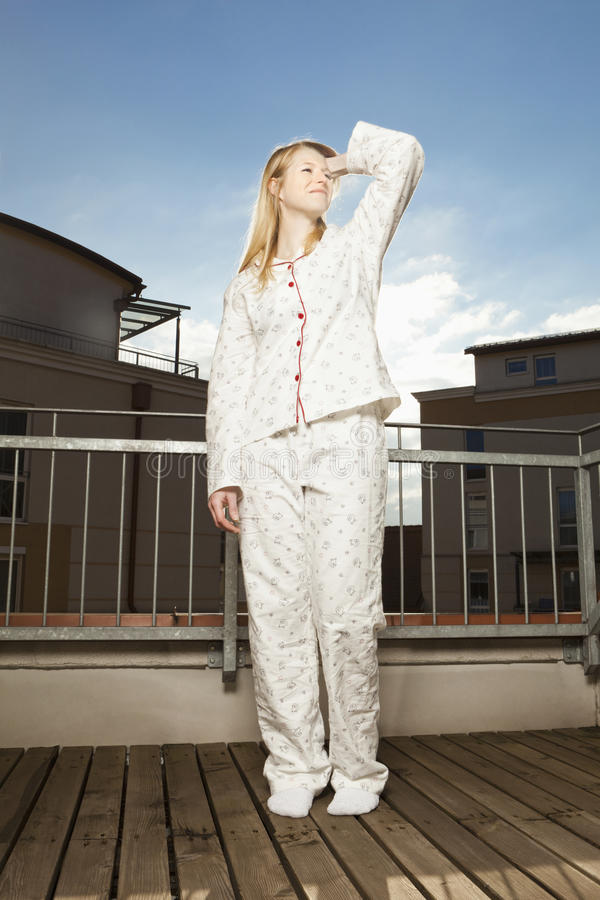 Woman start´s in a sunny day. Young woman in pajamas stands on the balcony and enjoys the sunshine stock image