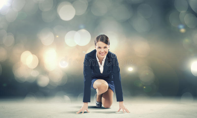 Woman at start. Young pretty businesswoman in suit ready to run stock photography
