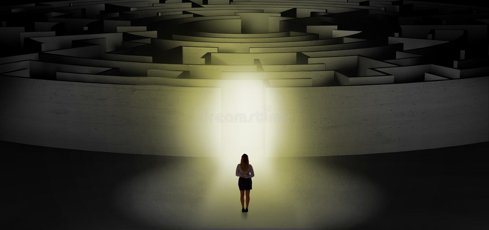 Woman starting a concentric labyrinth. Woman getting ready to enter a concentric labyrinth with lighted entrance concept stock photography