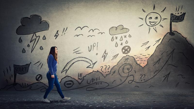 Woman conquering quest. Woman starting a life quest with obstacles. Self overcome imaginary climbing mountain with ups and downs, conquering for reaching royalty free stock photo
