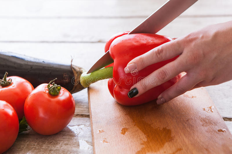 Woman starts to cut red pepper on wooden desk stock images