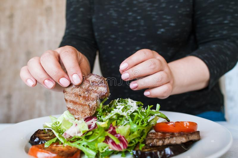 Woman starts to eat medallions with salad stock images