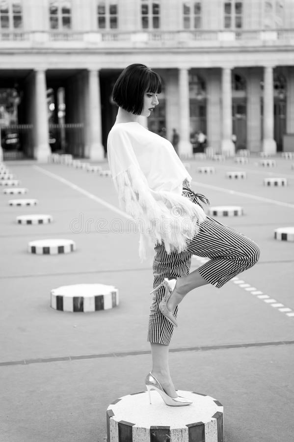 Woman stay on leg on square in paris, france. Girl in high heel shoes, fashionable clothes. Yoga pilates fitness, sport royalty free stock images