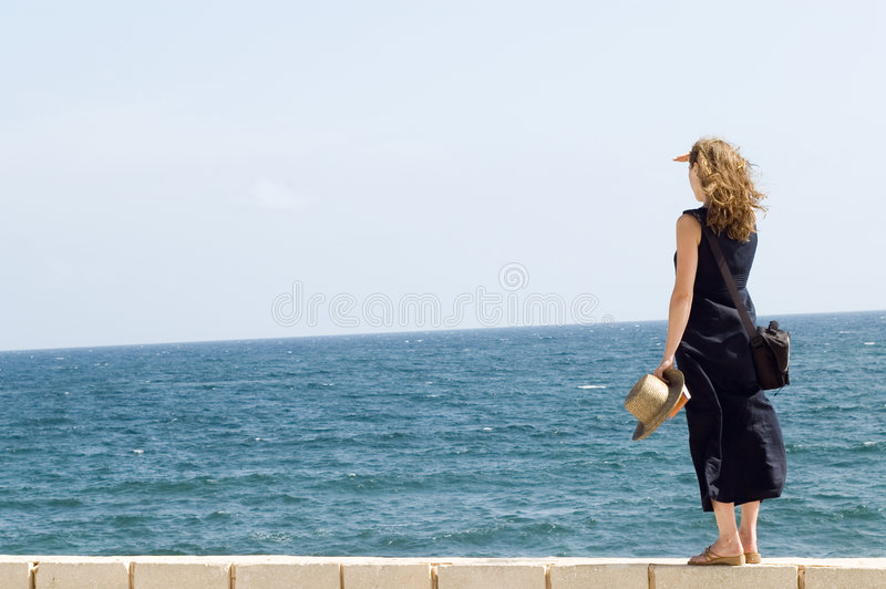 Woman staying on wall, watching at the sea stock photography