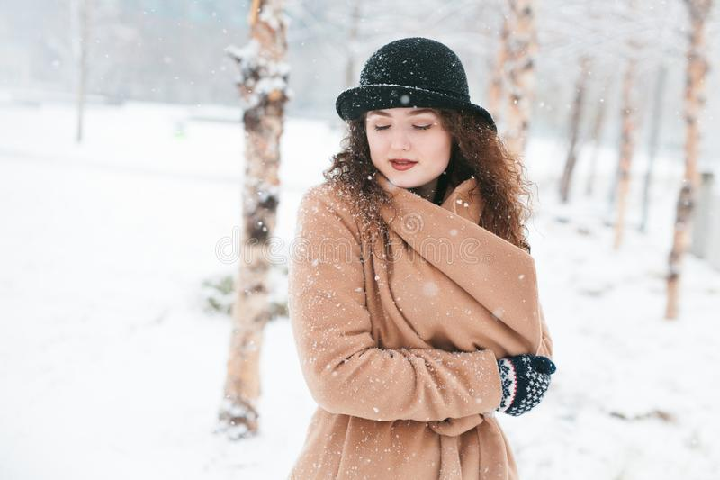 Woman staying warm during a snow storm royalty free stock images