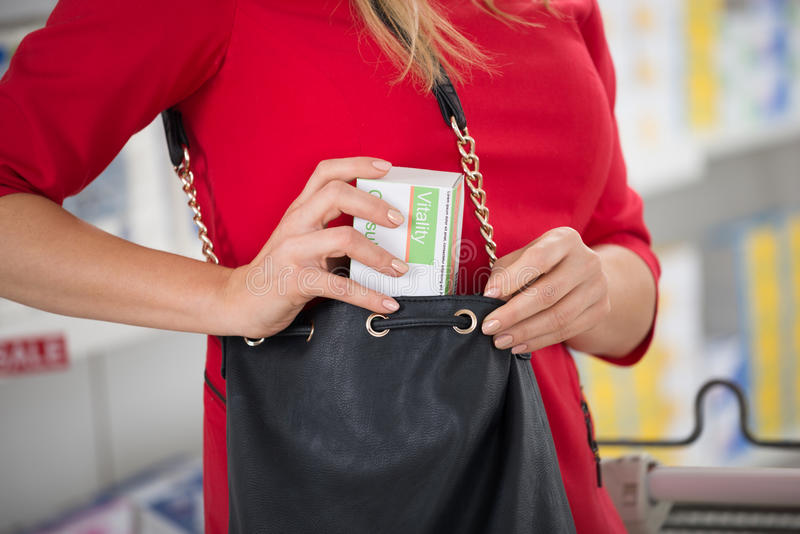 Woman Stealing Capsule Packet At Supermarket stock photo