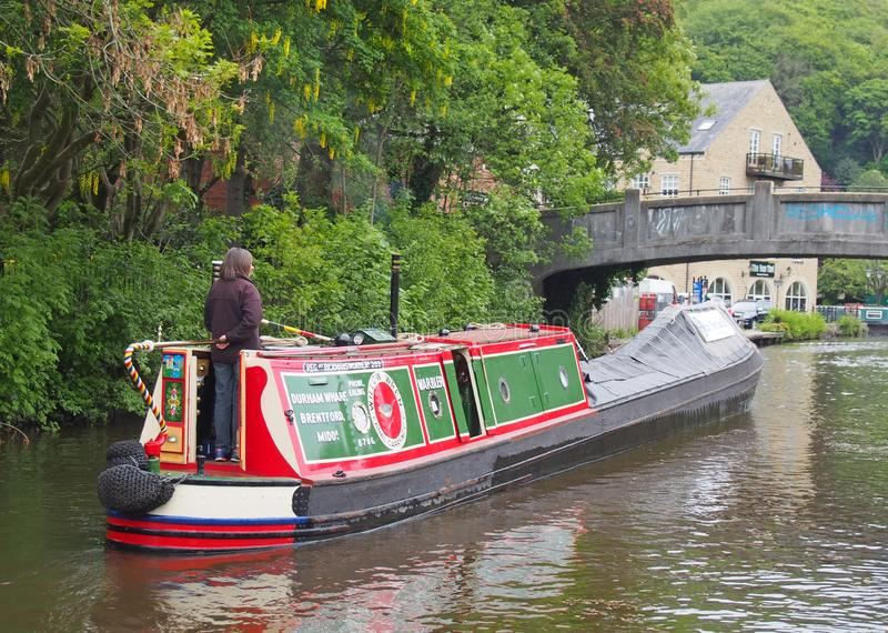 Woman steering an old barge going to the historic narrow boat club gathering held on the may bank holiday on the rochdale canal at. Hebden bridge, west yorkshire stock image
