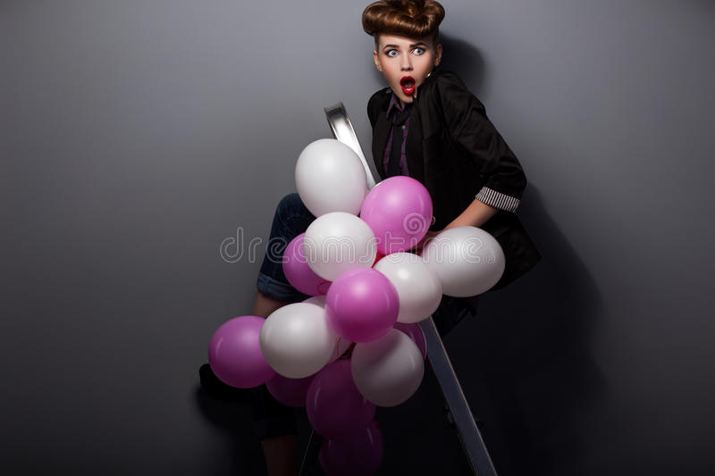 Woman on Step Ladder with Air Balloons Having Fun stock image