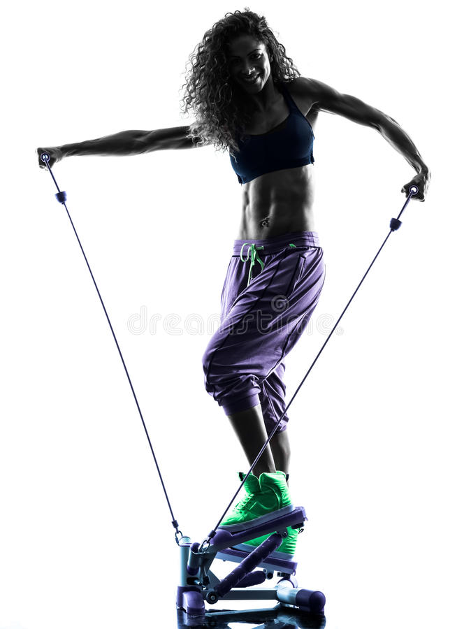 Woman Stepper fitness exercises silhouette. One african woman exercising Stepper fitness exercises in studio silhouette isolated on white background stock photo
