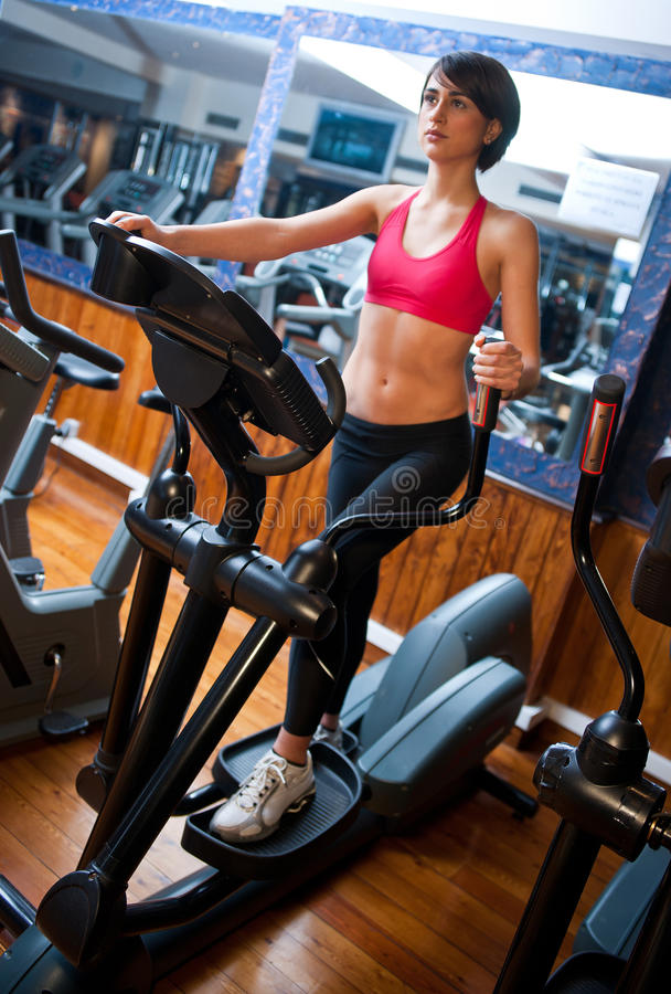 Woman on stepper in gym. Woman workout on stepper machine in the gym stock photos