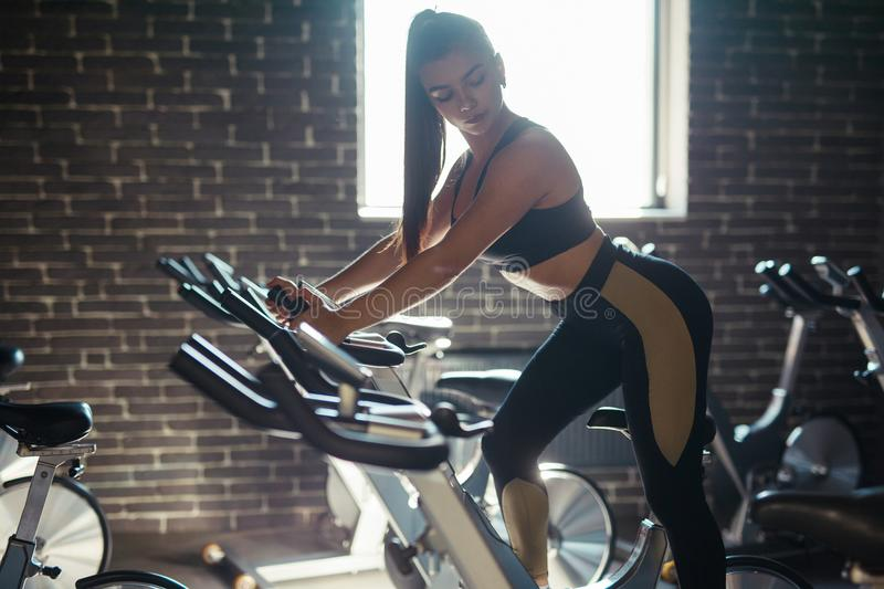 Woman on stepper. Pretty young woman doing exercises using stepper in gym royalty free stock image