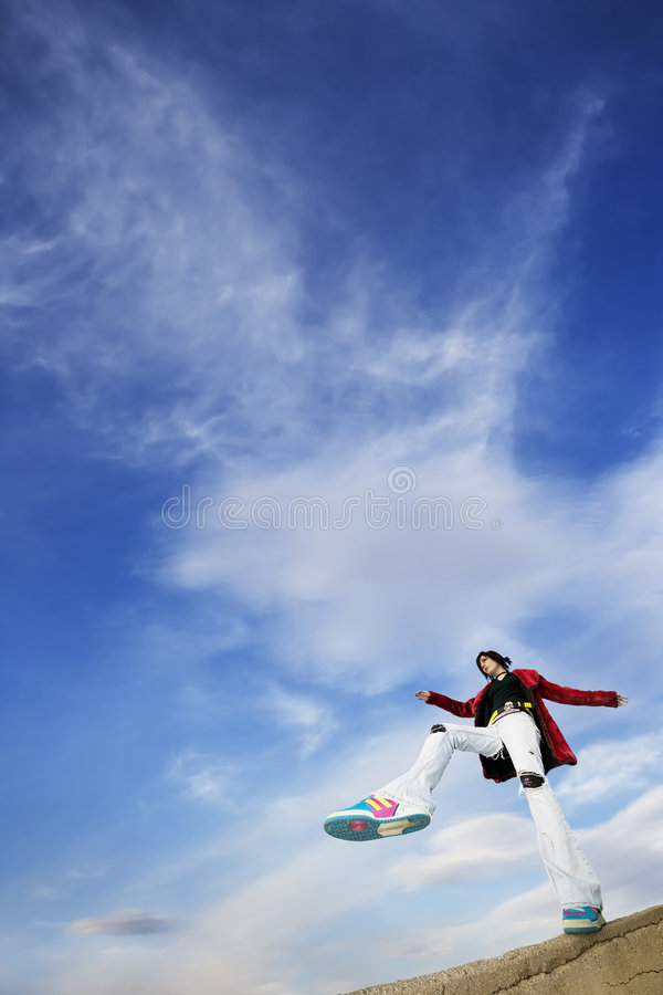 Woman Stepping Against the Sky. Wide angle shot of woman taking a big step against a cloudy sky royalty free stock image