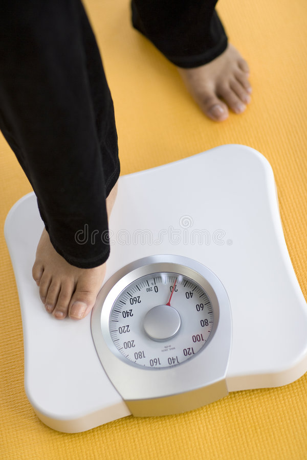 Woman stepping on scale. African American Woman weighing herself on a bathroom scale royalty free stock images