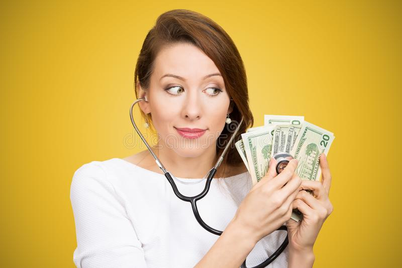 Woman with stethoscope listening to dollar bills making analysis of money†investment royalty free stock images