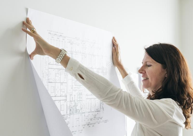 A woman sticking a blueprint to the wall stock images