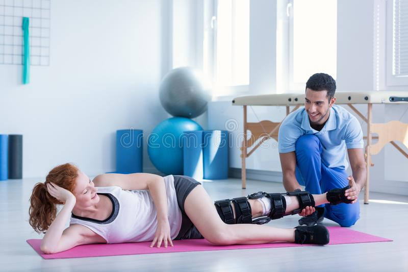 Woman with stiffener on the leg exercising during treatment stock images
