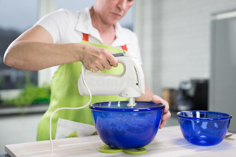 Woman is stirring dough in a blueish bowl in her modern kitchen stock photos